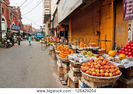 KOLKATA, INDIA - JAN 16, 2016: Marketplace with fresh fruits stall in a dirty street of old city on January 16, 2013 in Kolkata India. Total population of Kolkata metropolitan area is 13216546 people.