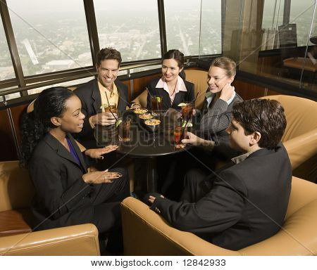 Ethnically diverse businesspeople sitting at table in restaurant talking.