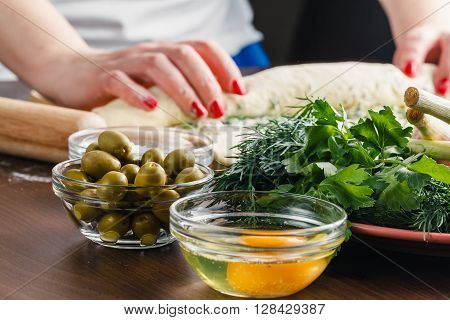 Woman hands cooking olives stuffed french bread