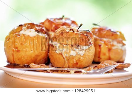 Closeup photo of a tasty baked apples stuffed with cheese cream, flavored with cinnamon, nuts and honey, served on the plate with a silver spoon, healthy nutrition, delicious fruit dessert