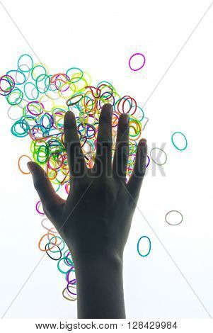 Colorful rubber bands under the kid's hand. Children's hobbies and favorite activities.