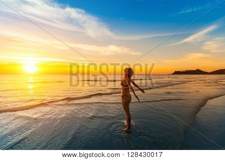Girl basking in the sun on the beach near the water during sunset.