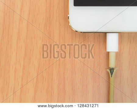 Top view of broken charger cable with smart phone on the wooden table with copy space