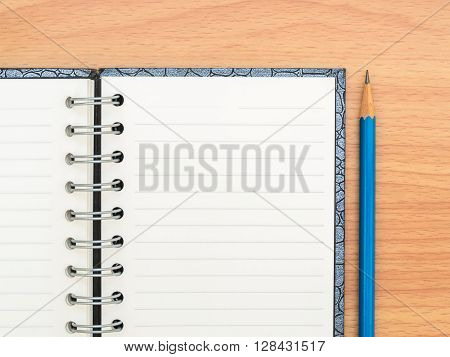 Top view empty notebook and blue pencil on wooden texture background