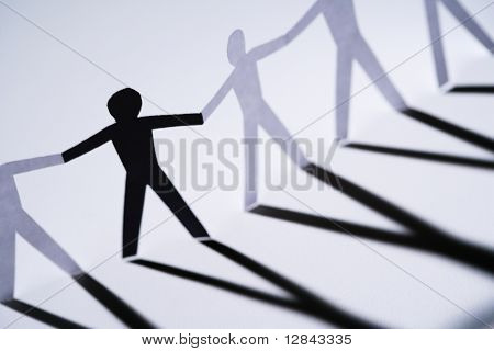 One black cutout paper person holding hands with group of white people.