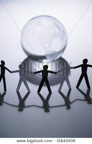 Black and white cutout paper people standing aroung Earth globe holding hands.