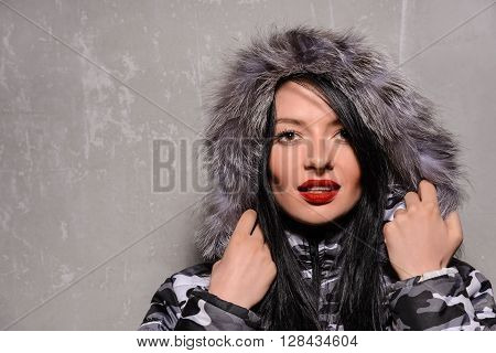 Sweet young woman in warm winter jacket with fur hood isolated on grey background.
