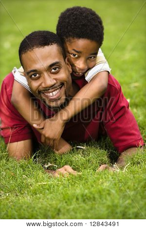 Father lying in grass smiling as son climbs on his back and hugs his neck.