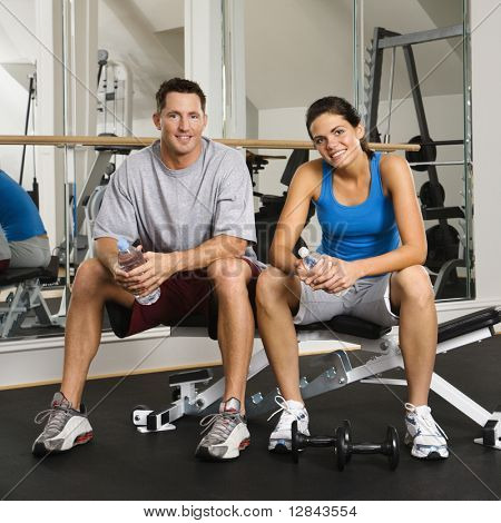 Man and woman sitting on exercise machine smiling holding water bottles.