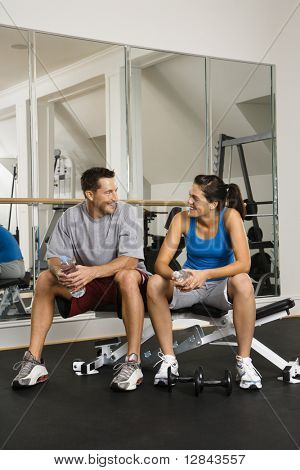 Man and woman sitting on exercise machine talking holding water bottles.