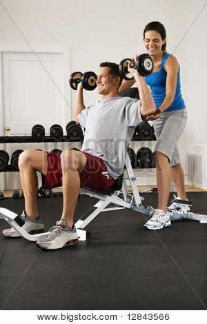 Woman assisting man lifting weights at gym.