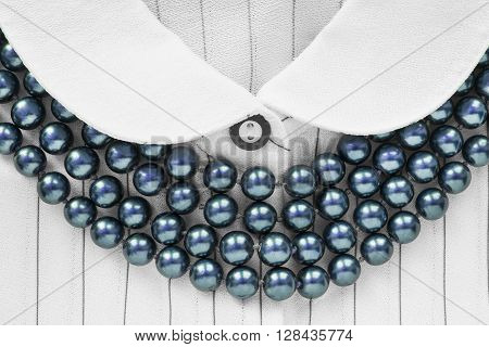 Strings of blue beads on white silk blouse closeup