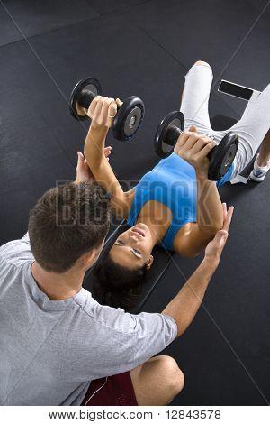Man assisting woman lifting weights at gym.