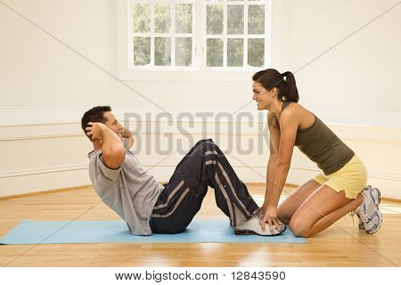 Woman holding man's feet down as he does sit up exercises.