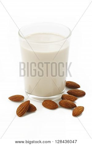 almond milk in glass with almonds on background