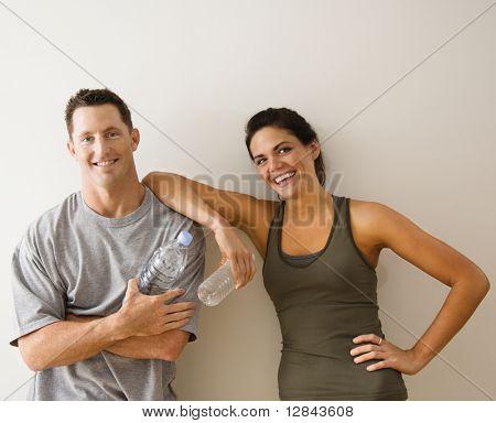 Mann und Frau in Fitnessstudio in Fitness Kleidung halten Wasser Flaschen stehend gegen Wand lächelnd.