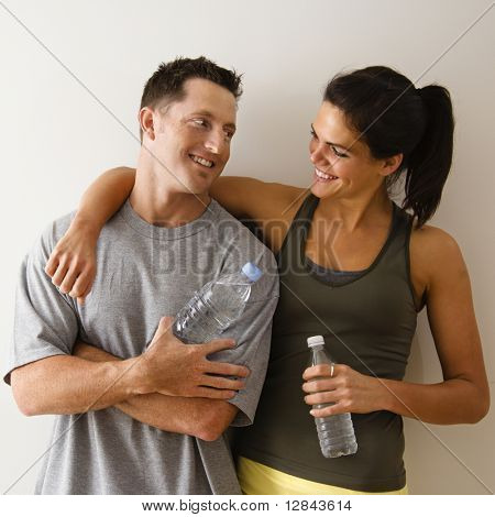 Man and woman at gym in fitness attire holding water bottles standing against wall smiling at eachother.