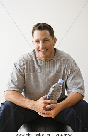 Man holding water bottle sitting on balance ball at gym smiling.