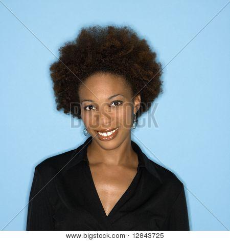 Kopf und Schulter Studio Portrait of happy smiling Woman auf blauem Hintergrund.