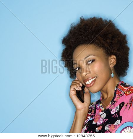 Woman with afro wearing vintage print fabric smiling holding cellphone.