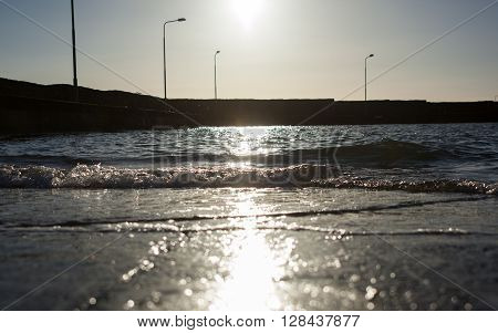 Sun shining on the shore of the harbor
