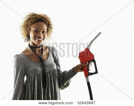 Portrait of pretty young woman smiling holding gas pump nozzle on white background.
