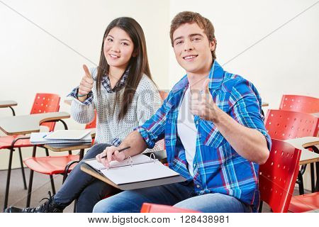 Two successful students with thumbs up in a classroom