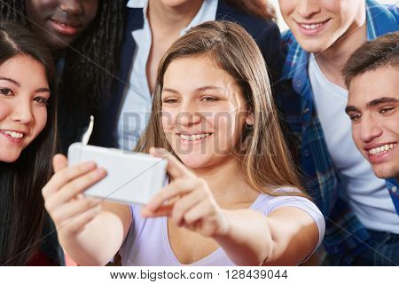 Happy teenagers take a selfie with their smartphone at school