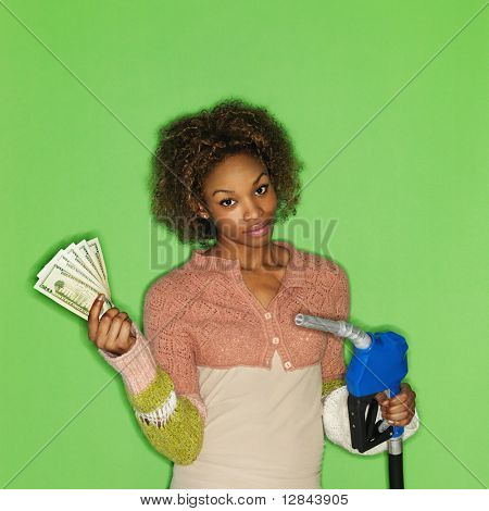 Portrait of pretty young woman standing against green background holding gasoline pump nozzle and money.