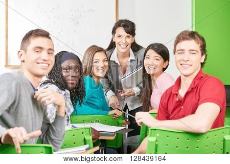 Teenage students with teacher in class at school