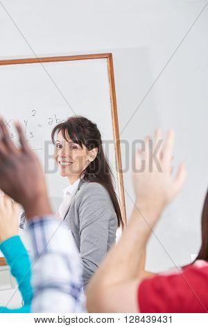 Teacher giving a class and students raising their hands