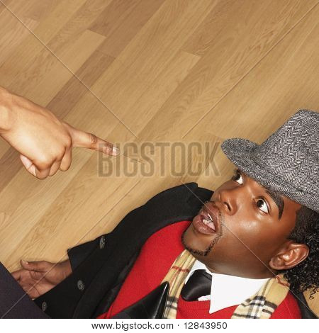 Man on back on floor with woman pointing accusingly.
