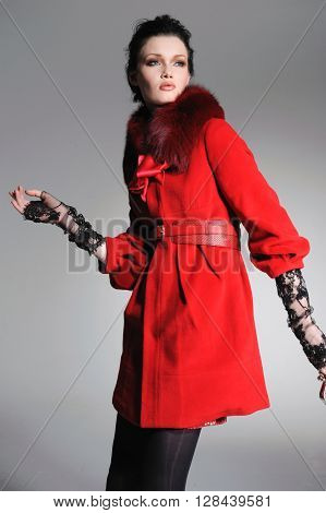 fashion model in red coat clothes posing in studio