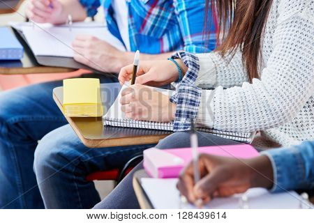Pupils take notes with their notebooks in school