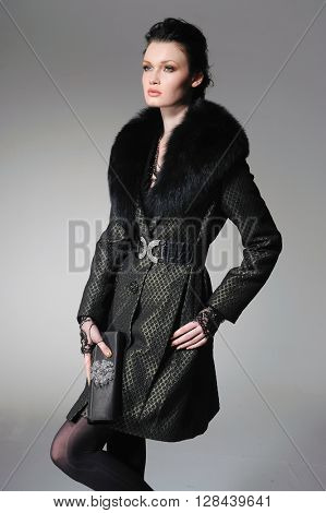 fashion model in black coat clothes posing in studio