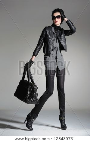 full-length fashion model in modern clothes holding handbag posing
