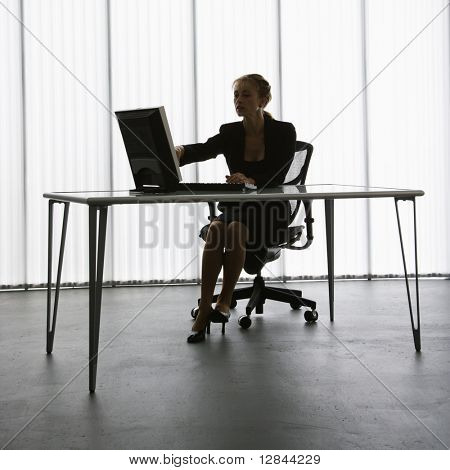 Silhouette of Caucasian businesswoman sitting at desk with computer working.