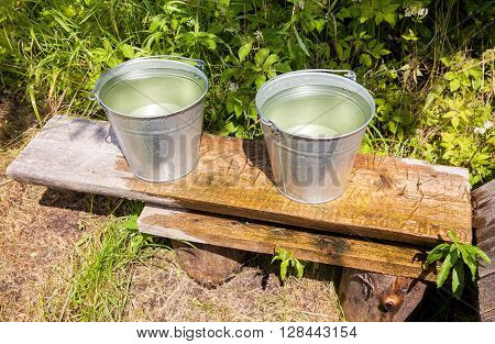 Metal buckets with cold water standing on a bench at the village water well
