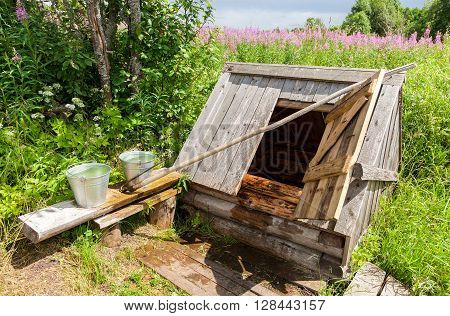 Village wooden water well with the open door and a metal buckets of water in the summer sunny day