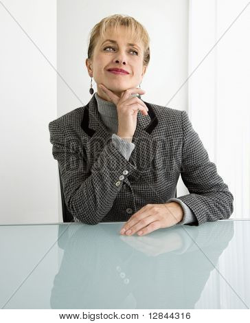 Caucasian woman sitting at desk with hand to chin smiling and making facial expression.