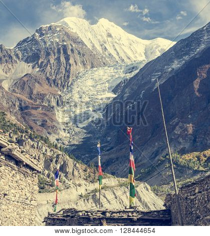 Praying flags blowing in the wind infront of a glacier. Annapurna region in Nepal.