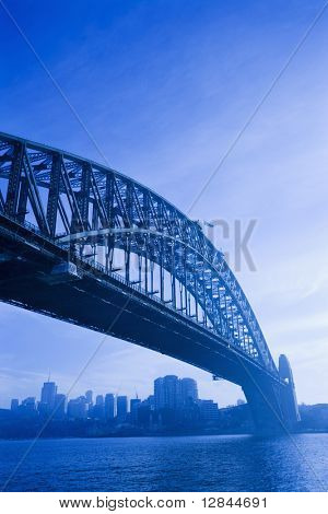 Low angle view of Sydney Harbour Bridge in Australia with view of harbour and downtown skyline.