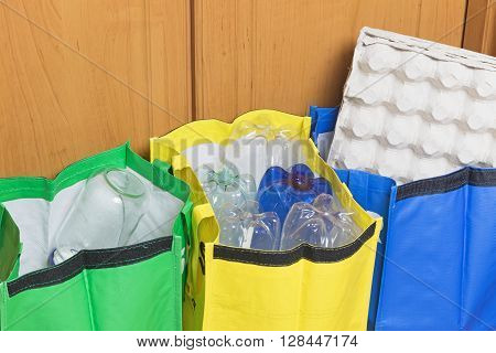 Green blue and yellow bags for sorting household waste are filled with waste - paper plastic and glass.