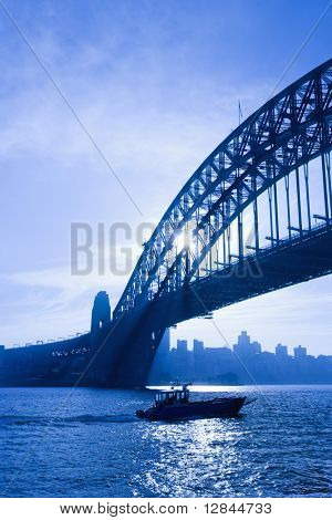 Boat under Sydney Harbour Bridge at dusk with view of distant skyline and harbour in Sydney, Australia.