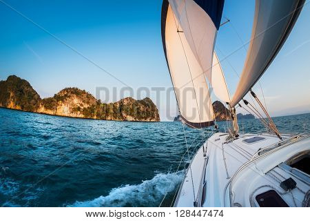 Sailing boat moves in the tropical sea towards the limestone mountains