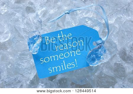Light Blue Label With Blue Ribbon On White Transparent Curshed Ice Cubes As Background. English Quote Be The Reason Someone Smiles For Cool Greetings.Close Up Or Macro View.