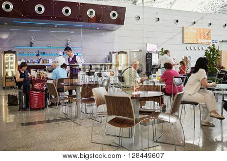 RUSSIA, MOSCOW - AUG 11, 2015: People at tables in cafe of Moscow Vnukovo International Airport. Moscow Vnukovo International Airport is the third busiest airport in Russia.