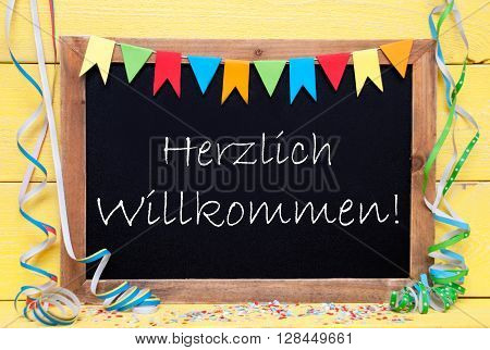 Chalkboard With German Text Herzlich Willkommen Means Welcome. Party Decoration Like Streamer, Confetti And Bunting Flags. Yellow Wooden Background With Vintage, Retro Or Rustic Syle
