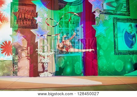 RUSSIA, KRASNOGORSK - DEC 12, 2014: Young female gymnast performs in the gala concert of Moscow open all-russia festival Star Children on the stage in the House of Moscow Oblast Government.
