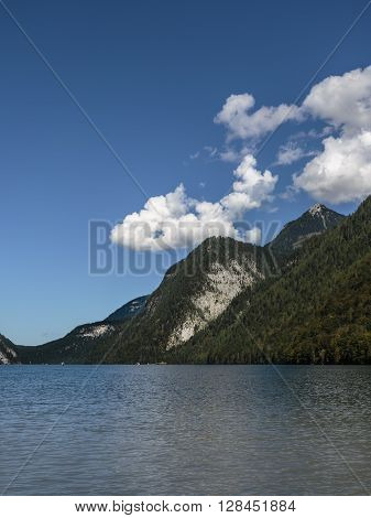 view over Koenigssee to densely wooded hills an mountains from the sun illuminated rocks clear blue sky with large white clouds